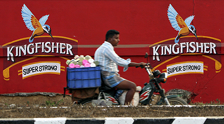 A man on a motorbike rides past the factory of United Breweries Ltd (UB) that manufactures Kingfisher beer in Thiruvalluar district, Tamil Nadu.
