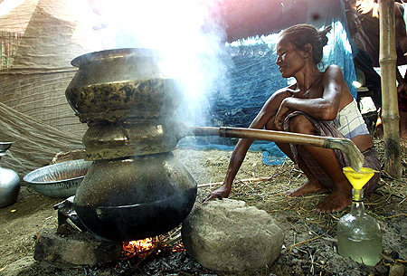 A Bodo tribal woman prepares rice wine inside a relief camp in Madnabori 70 kms (43 miles) north east of the city of Guwahati.