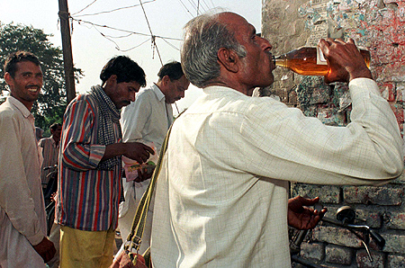 A man gulps down liquor outside a wine shop while others stand in a queue to buy liquor in Rewari, Haryana.