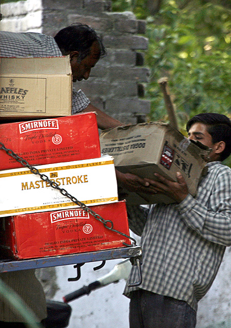 Labourers unload alcohol boxes from a truck outside a wine shop in Srinagar.