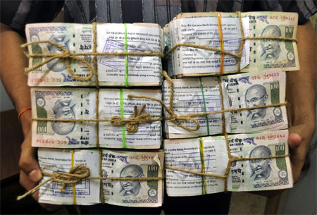 A banker carries stacks of rupee notes.