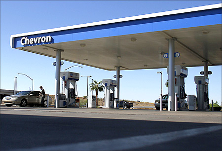 A motorist stands outside of his car at a Chevron gas station in Buckeye, Arizona.