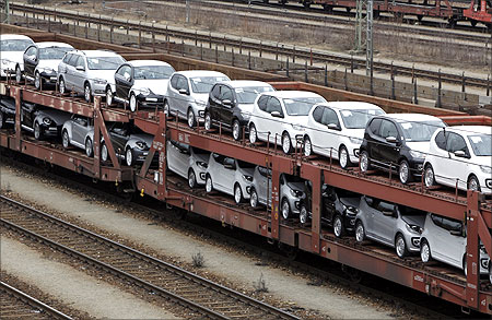 New cars by German car manufacturer Volkswagen AG stand on wagons at a train station in Munich.