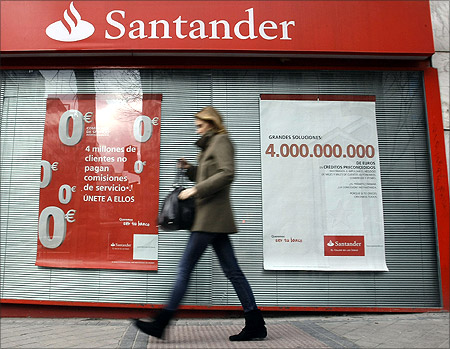 A woman walks past a Santander bank branch in central Madrid.