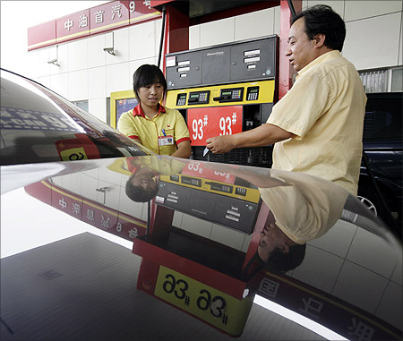 A taxi driver waits to fill up a car at a PetroChina gas station in Beijing.
