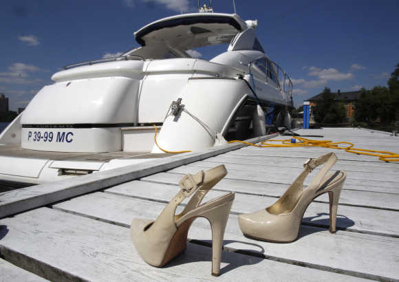 A pair of high heel shoes is placed on shore in front of a yacht.
