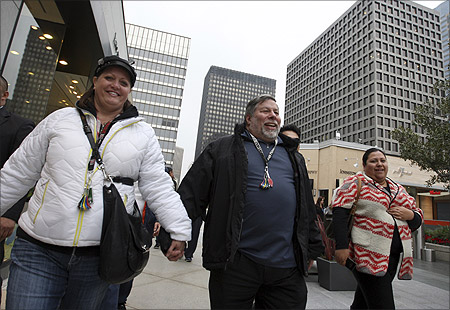 Apple co-founder Steve Wozniak (C) and his wife Janet walk hand-in-hand to the store entrance after waiting in line overnight with customers to purchase the new iPad at the Apple Store in Century City Westfield Shopping Mall in Los Angeles, California.