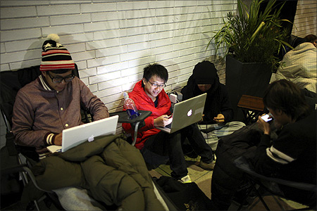 Gordan Cheng uses his iPhone and Mac computer while waiting in line overnight to purchase the new iPad at the Apple Store in Century City Westfield Shopping Mall in Los Angeles, California.