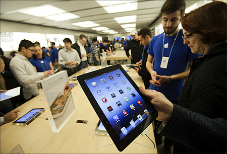 Customers look at the the new iPad at the Apple Store at the Toronto Eaton Centre shopping mall in Toronto.