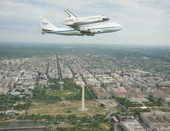 Space shuttle Discovery, mounted atop a Nasa 747 Shuttle Carrier Aircraft, flies over the Washington skyline.
