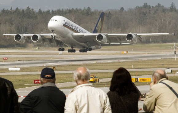 People watch an Airbus A380 jet of Singapore Airlines taking off from the airport in Zurich.