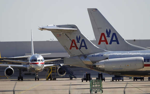 American Airlines airliners sit near a hanger at Dallas/Fort Worth International Airport, Texas.