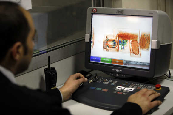 A security official looks at a screen displaying X-ray screened parcels in Turkish Post's postal logistic centre at the Ataturk International airport.