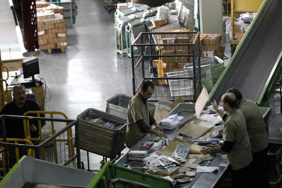 Workers sort mail and parcels in one of the Turkey's regional postal logistic centre in Ankara.