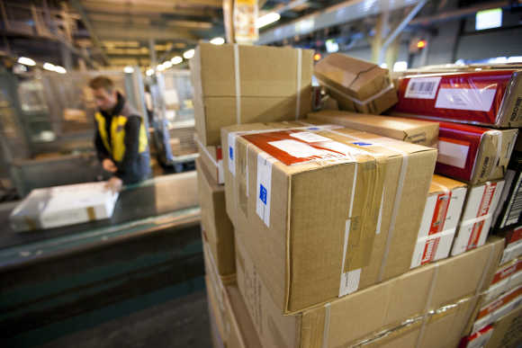 A Swiss post employee lines up parcels on a conveyer belt in Daillens near Lausanne.