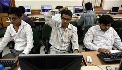 Brokers trade on their computer terminals at a brokerage firm in Mumbai.