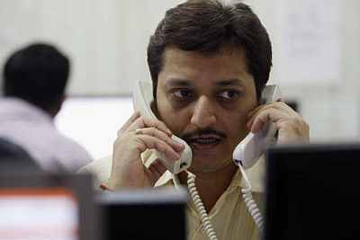 A trader speaks on phones while trading at a stock brokerage in Mumbai.