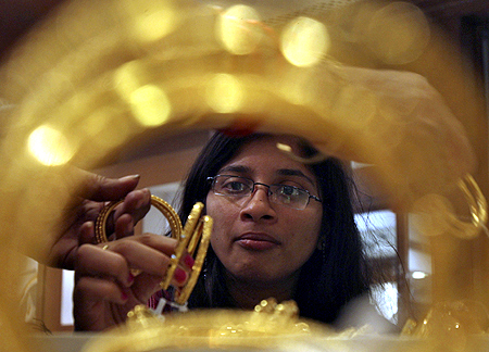 customer looks at gold bangles inside a jewellery showroom in the southern Indian city of Hyderabad.