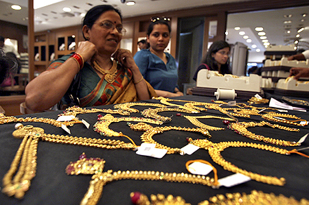 A customer tries on a gold necklace inside a jewellery showroom in the southern Indian city of Hyderabad.