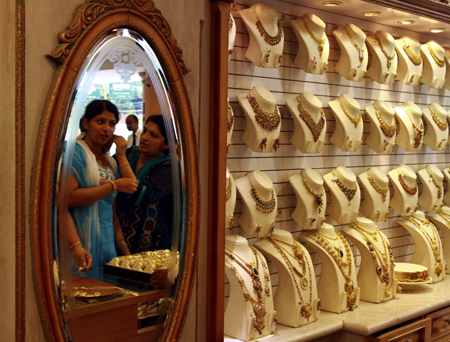 A woman tries a gold earring inside a gold jewellery showroom in Kochi.