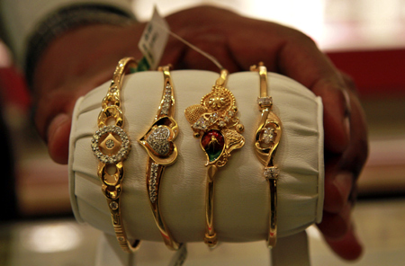 A salesman displays gold bangles to a customer at a jewellery showroom in Chennai.