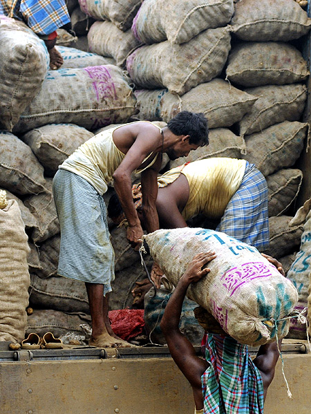 Labourers unload sacks of potatoes from a truck at a wholesale market in Agartala.