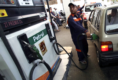 An employee fills a car with petrol at a gas station in Jammu.