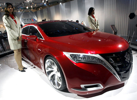 This file photo shows models standing next to Maruti-Suzuki's Kizashi, concept car.