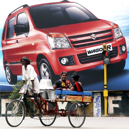 A rickshaw-puller peddles in front of a billboard for the WagonR, a car manufactured by Maruti Suzuki.