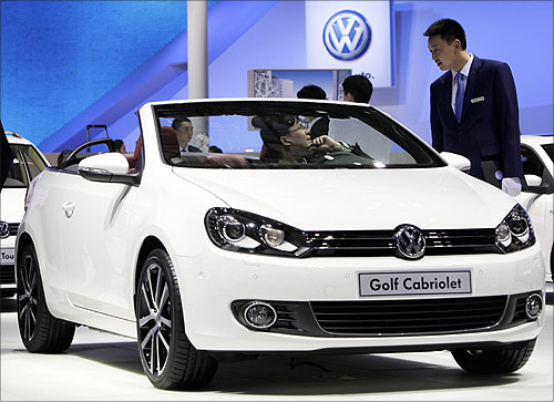 A visitor sitting in a Volkswagen Golf Cabriolet speaks to a staff member at Auto China 2012 in Beijing.