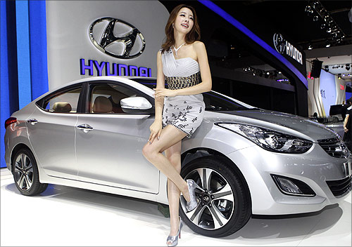 A model stands next to a Hyundai Elantra at Auto China 2012 in Beijing.