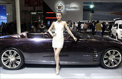 A model stands next to a Cadillac CIEL concept car at Auto China 2012 in Beijing.