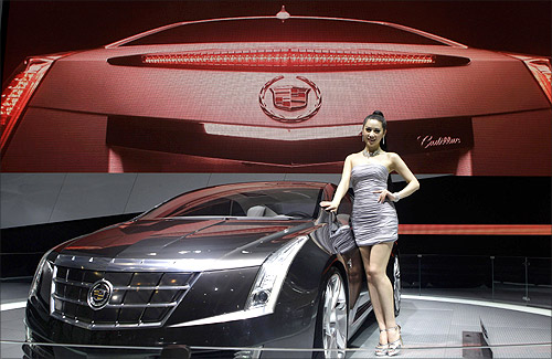 A model stands next to a Cadillac ELR at Auto China 2012 in Beijing April 24, 2012.