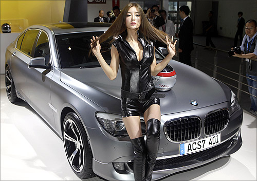 A model sits on a BMW 530i AC Schnitzer car at Auto China 2012 in Beijing.