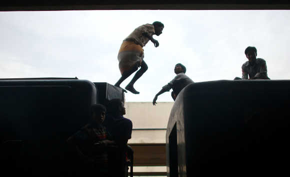 A commuter jumps between cars on a train at the Kamalapur Railway Station, the largest in the country, in Dhaka, Bangladesh.