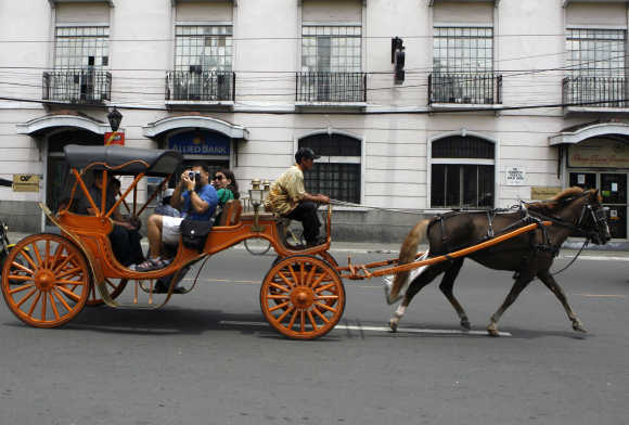 Tourists ride on a 'Kalesa', a horse-drawn carriage, in Manila's historic Intramuros also known as Walled City.