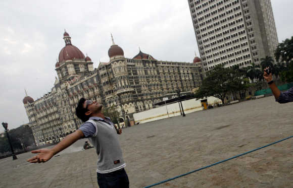 A visitor poses for a picture in front of Taj Mahal hotel in Mumbai.