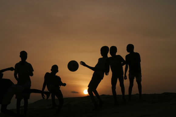 Children playing soccer are silhouetted at sunset in Nigeria's main city of Lagos, Nigeria.