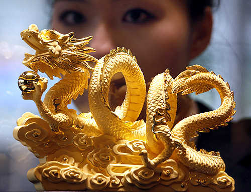 A sales representative poses behind a nine-tael 24K gold in the shape of a dragon forming the numerals 2012.
