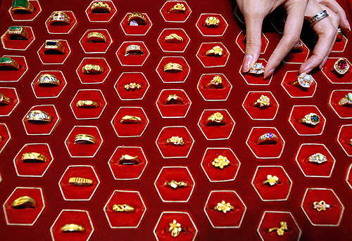 A shopkeeper poses with gold rings inside a jewellery shop in Taipei.