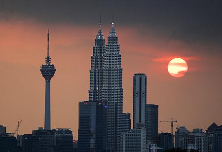 The sun sets near the Petronas Twin Towers and Kuala Lumpur Tower (left).