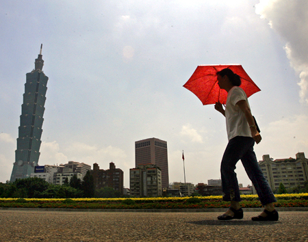 A woman walks past the Taipei 101 building in Taipei.