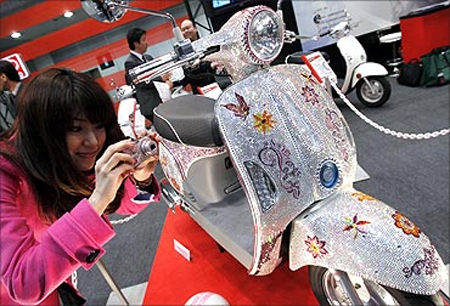 A woman takes a picture of Kymco scooter Mitch, studded with 100,000 Swarovski crystals.