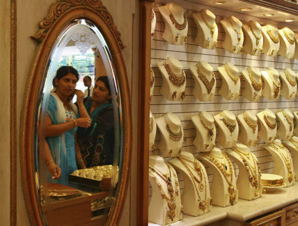 A woman is reflected in a mirror as she tries a gold earring inside a jewellery showroom in Kochi.