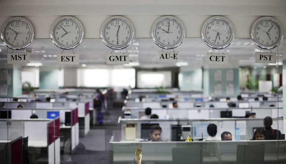 Workers are pictured beneath clocks displaying time zones in various parts of the world at an outsourcing centre in Bangalore.