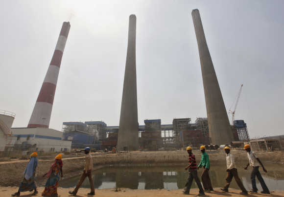 Workers walk inside the Jindal Power and Steel complex at Nisha village in Orissa.