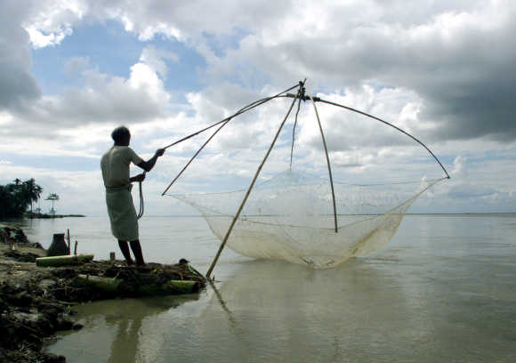 A fisherman arranges his net to fish on the waters of Bhramputra River in Simna.
