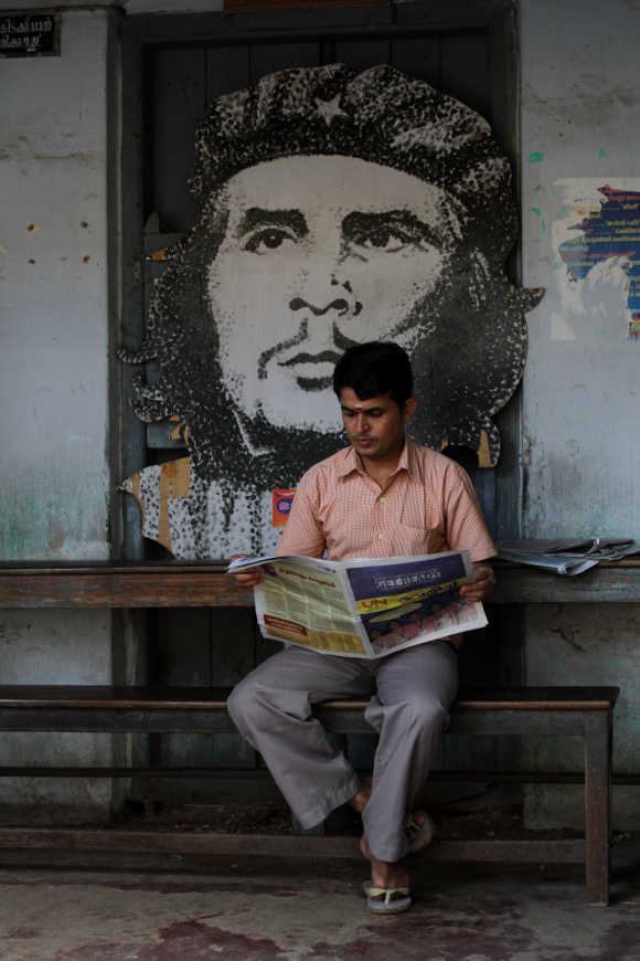 A man reads a newspaper in front of a cardboard cutout of Ernesto Che Guevara in Kerala.