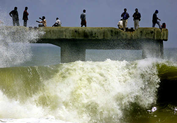 Indians enjoy the splash of huge sea waves from a bridge in Thiruvananthapuram..