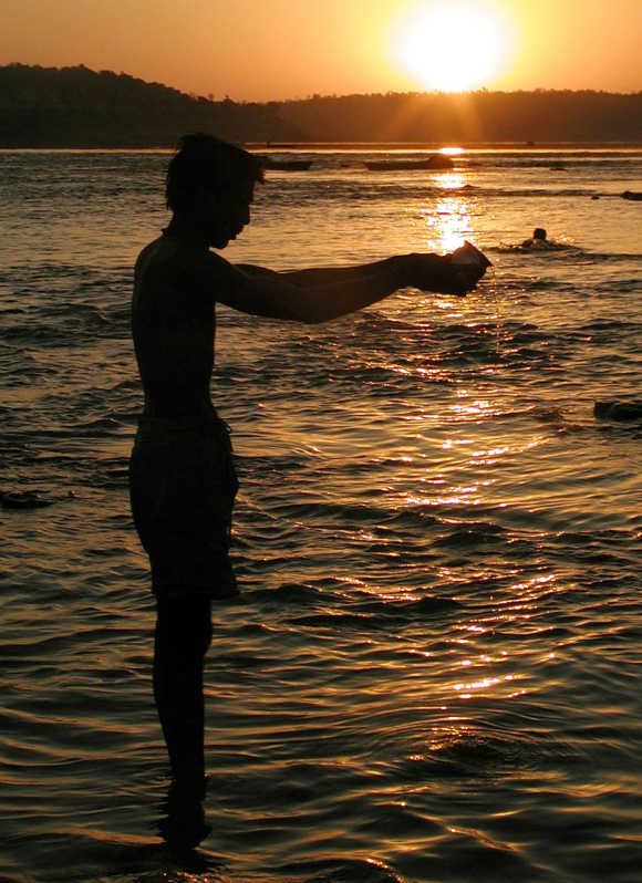A man offers water to the sun along the river banks near Indore.
